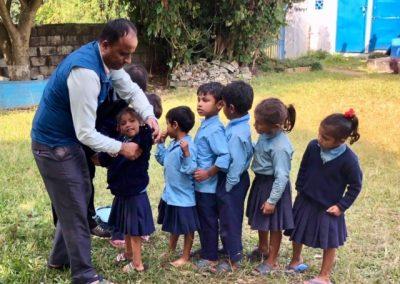 Maths teacher helping the little ones put their jumper on